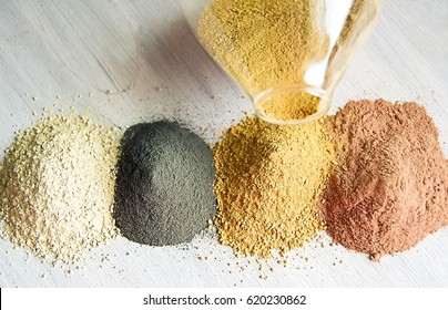 Yellow, red, white and black cosmetic cleansing clay for face and body. Healing Clay is a natural product. Dry cosmetic clay on a wooden background. Selective focus