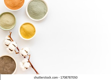 Yellow, red, white, blue and black cosmetic clay on white table top view copy space