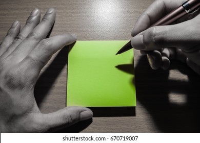 the yellow reminder pad put on table is holding by hand and writing on it. the color tone is pale color except color of paper is yellow. This note for remind your activities and event do not forget