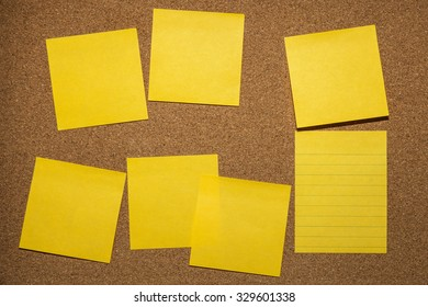 yellow reminder sticky note on cork board, empty space for text