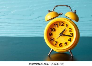 yellow retro alarm clock on wood background photo