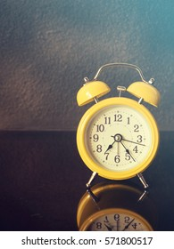 yellow retro style alarm clock on black reflect floor