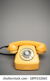 yellow and retro telephone on grey background