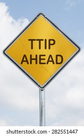 yellow rhomb traffic sign at a silver metal mast with the words TTIP ahead in front of a blue sky with white clouds. Business and financial concept for international trade between Europe and USA