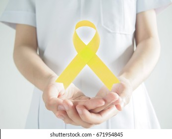Yellow ribbon awareness symbol levitating above female health professional hands in white uniform for bone cancer, bladder cancer, liver cancer, endometriosis and suicide prevention concept.