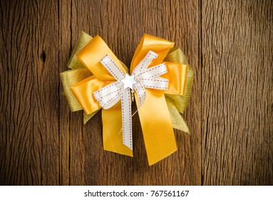 Yellow ribbon gift bow on wooden board background,satin bow