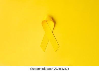 Yellow Ribbon on yellow background for supporting people living and illness. September Suicide prevention day, Childhood Cancer Awareness month and World cancer day concept