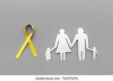 Yellow ribbon for suicide and endometriosis awareness near paper silhouette of family on grey background top view