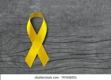 Yellow ribbon symbolic for Sarcoma Bone cancer, Spina Bifida Awareness Month and suicide prevention on helping hand