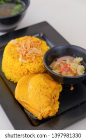 Yellow rice and chicken with soup and white background