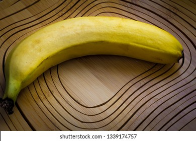a yellow ripe banana is lying on a wooden board, probably it will be cut because it lies on a cutting board