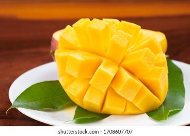 Yellow ripe mango on white plate.