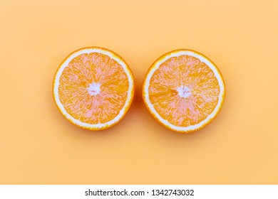 Yellow ripe orange slices, top view. Two halves of fresh juicy orange fruit on orange paper background with copy space. Health and beauty.
