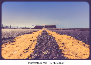 Yellow road dividing lines on rugged road along the California coast with vintage retro filter effect