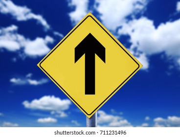 Yellow road sign with cloudscape with arrow symbol