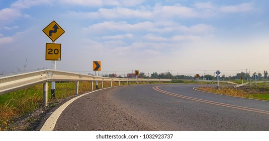 Yellow road sign symbol on curve way and bright blue sky