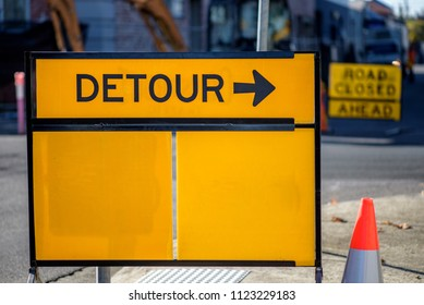 A yellow road sign with the word DETOUR and a arrow pointing to the right.