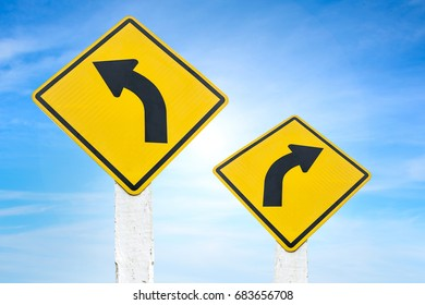 Yellow road signs indicating left and right turn with blue sky background.