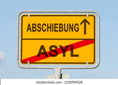 yellow road or town sign informing in german that asylum is behind and deportation is ahead. Concept for national separation policy in Europe
