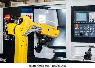 Yellow robot hand in CNC machine center , automatic working process