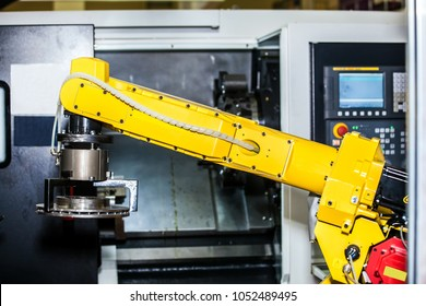 Yellow robot hand in CNC machine center, automatic working process