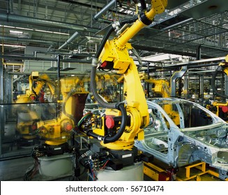 yellow robots welding cars in a production line