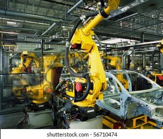 Gelbe Roboter, die Autos in einer Produktionslinie schweißten