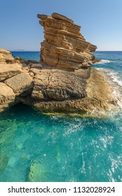 Yellow rock in blue sea at triopetra beach in crete