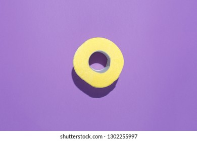 Yellow roll of toilet paper on a purple background. Flat composition, top view.