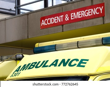 The yellow roof of an NHS ambulance parked outside the A&E department of a hospital in England, UK, with its emergency lighting equipment bar and the Ambulance and Accident & Emergency signage