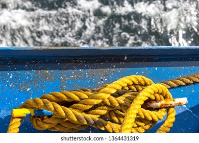A yellow rope, or a mooring line on a ship. The colour contrast of blue and yellow is beautiful and in the background you can see the sea.