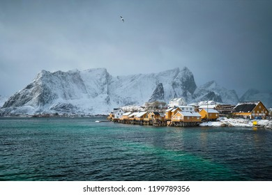 Yellow rorbu houses of Sakrisoy fishing village with snow in winter. Lofoten islands, Norway