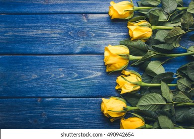 Yellow roses flowers on blue grunge wood.