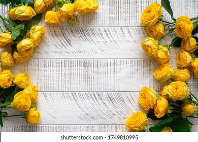 Yellow roses on the white wooden background. Top view. Copy space.