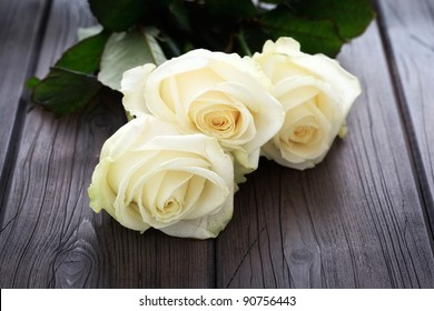 Yellow roses on a wooden background.