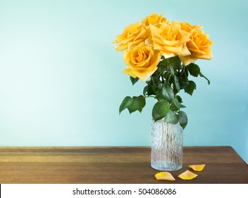 Yellow roses in a retro glass vase on wood table
