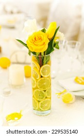 Yellow roses in vase with sliced lemon