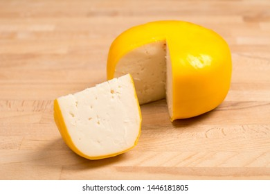 Yellow round cheese. Dutch goat cheese with pieces on wooden background.