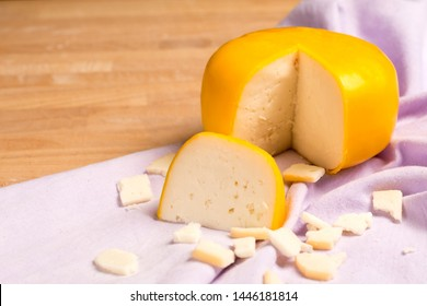 Yellow round cheese. Dutch goat cheese with pieces on wooden table.