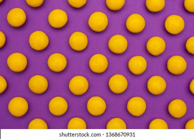 Yellow round chocolate candies on a purple background
