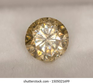 Yellow round faceted moissanite on the background