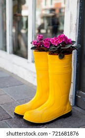 Yellow rubber boots as advertisement in a shopping street with purple flowers