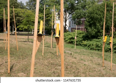 Yellow rubber boots on wooden stilts in the park. Abstract decoration