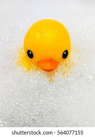 yellow rubber duck in bath swimming in foam water