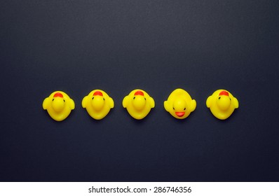 Yellow rubber ducks aligned in a line one pointing in a different direction over dark grey background, above view