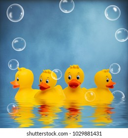 Yellow rubber ducks swimming in water with bubbles surrounding them.  Their reflections can be seen in the water.  Blue textured backgorund with text area available.