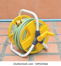 Yellow rubber hose reel with white stand. Gardening equipment.