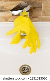 Yellow rubber hygienic gloves hanging on inox water tap