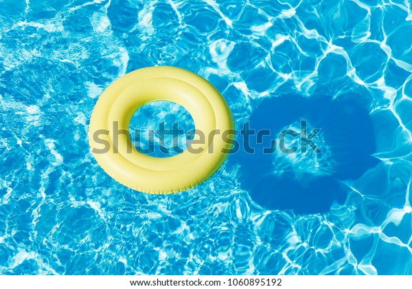 Yellow rubber ring floating on the water surface