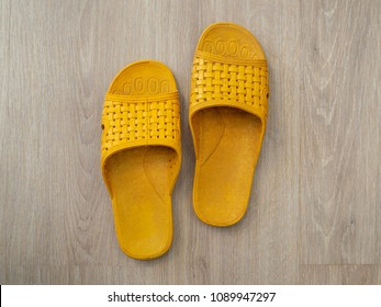 Yellow Rubber Sandals Flip Flops on Bright Wooden Background Top View